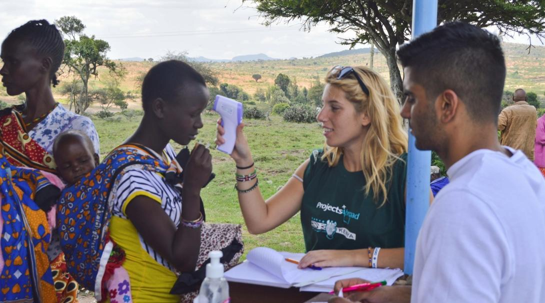 A Projects Abroad intern pictured checking the temperature of local residents as part of her nursing internship in Kenya.
